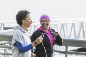 Two African-American women exercising together, jogging or power walking side by side. The senior woman with white hair is in her 60s. Her friend is in her 50s.